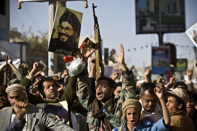 FILE - In this April 22, 2015 file photo, a Shiite rebel, second left, holds a poster of Hezbollah leader Sheikh Hassan Nasrallah as he attends along with hi...