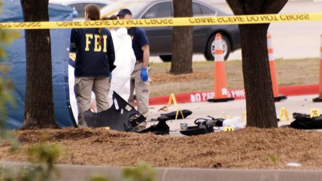 An FBI agent views the area where debris of a car was blown up by police as a precaution, near the Curtis Culwell Center on May 4, 2015 in Garland, Texas