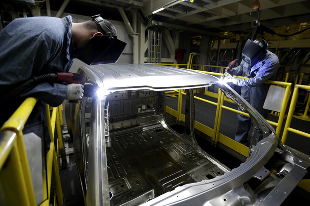In this March 13, 2015 photo, workers weld body panels on the new aluminum-alloy body Ford F-150 truck at the company's Kansas City Assembly Plant in Claycom...