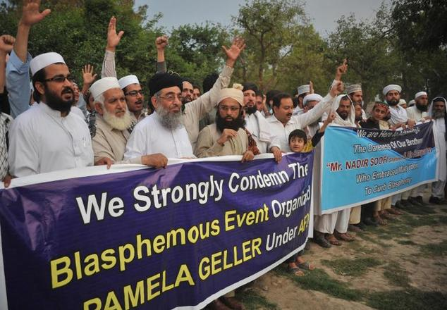 Pakistani residents shout slogans as they march behind a banner during a protest in Peshawar on May 5, 2015, against the anti-Muslim cartoon exhibition in Ga...