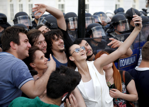 Protestors take a selfie in front of a police cordon during a demonstration in front of the Government building in Skopje Macedonia, on Tuesday, May 5, 2015....