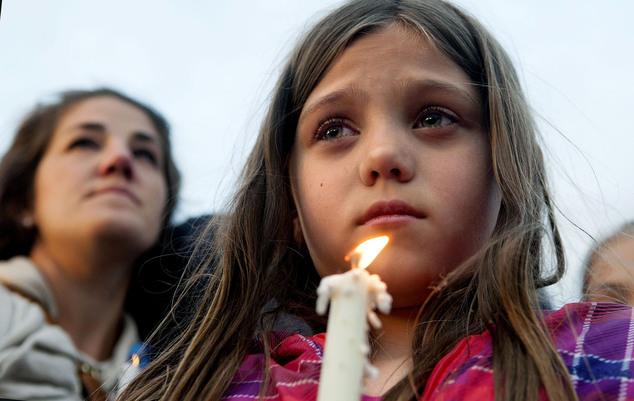 Maya Averill, 9, attends a candlelight vigil for Sgt. Greg Moore, a 16-year veteran of the Coeur d'Alene Police Department who was shot after checking on a s...