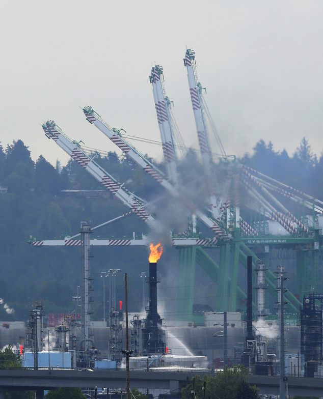 A fire burns at a U.S. Oil and Refining Co. facility Wednesday, May 6, 2015 at the Port of Tacoma in Tacoma, Wash. The Tacoma Fire Department says that no in...