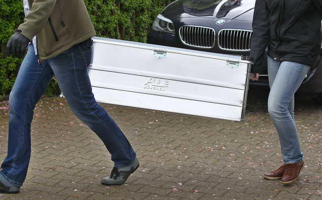 Police carry seized items from a house in Augsburg, southern Germany, Wednesday, May 6, 2015. German authorities conducted raids across the country, seizing ...