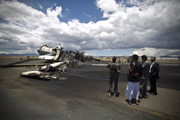 FILE - In this Tuesday, May 5, 2015 file photo, airport officials look at the wreckage of a military transport aircraft destroyed by Saudi-led airstrikes, at...