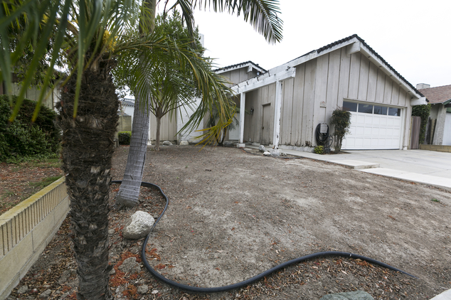 A home with a dead lawn is seen in Cypress, Calif., on Wednesday, May 6, 2015. California water regulators have imposed unprecedented mandatory water cutback...