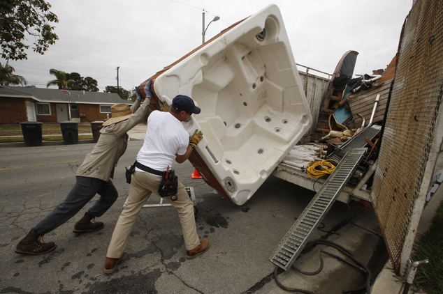 """Spa Removers' owner Lando Ferrenback, right, and worker, Juan Alexander remove a spa at a residence in which the owner considered it """"a waste of water,"""" in G..."""