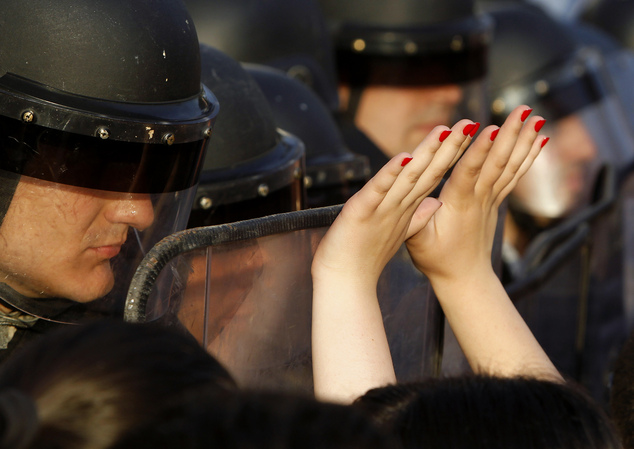 A woman lifts her hands up in front of the police during a protest in front of the Government building in Skopje Macedonia, on Tuesday, May 5, 2015. Macedoni...