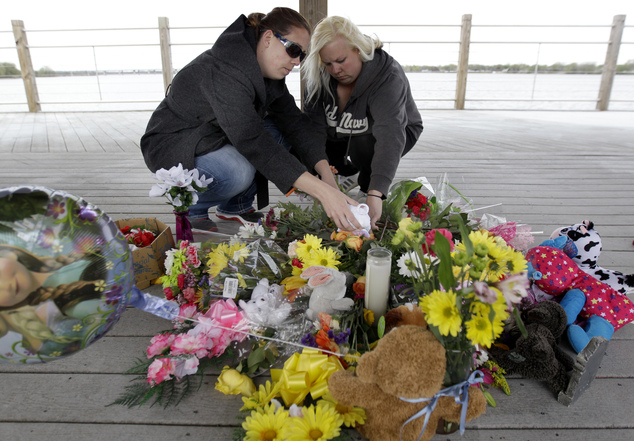 Jodi Meyer, left, and Sonia Meyer place flowers at a memorial in the pavilion on the re-opened Trestle Trail, on the east side of the trail near Fritse Park,...
