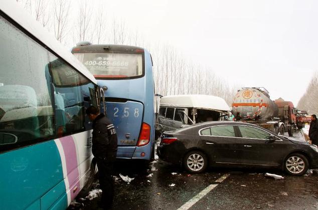 People check their damaged cars by the pile up of over 100 vehicles after a crash along a highway in Weifang, east China's Shandong province on December 8, 2011