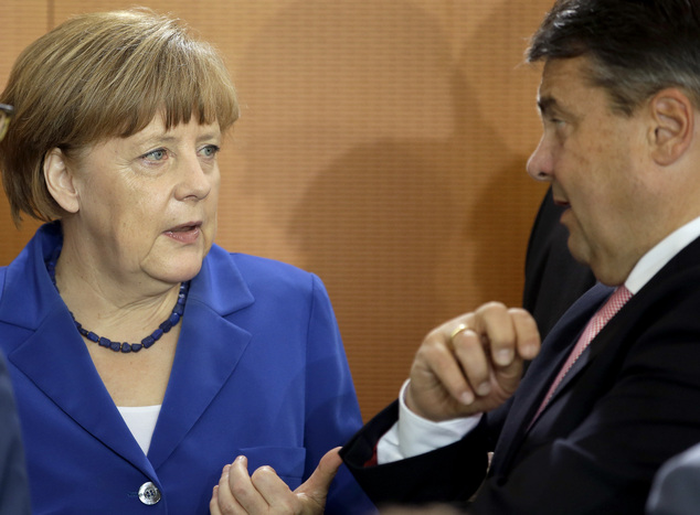 German Chancellor Angela Merkel, left, and Vice Chancellor and Economy Minister Sigmar Gabriel, right, talk as they arrive for the weekly cabinet meeting at ...
