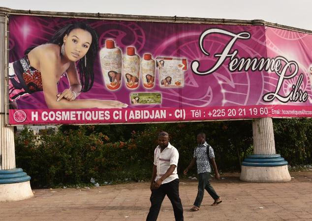 Two men walk under a giant advertisement for skin-lightening products in Abidjan on May 2, 2015