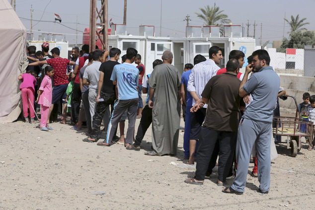 FILE - In this Thursday, April 30, 2015, file photo, displaced Iraqis wait in line to receive humanitarian aid at a camp set up for people from Ramadi and ar...