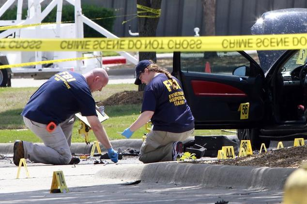 Investigators work a crime scene outside of the Curtis Culwell Center
