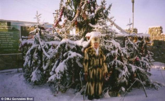 In another festive photograph Brzi is seen outside in front of a snow covered pine tree complete with decorations