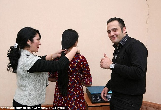 Alexander Kalendarev, owner of the Natural Human Hair company, gives the thumbs-up as a young woman has her long hair cut off. His business now employs 350 people in numerous factories processing human hair