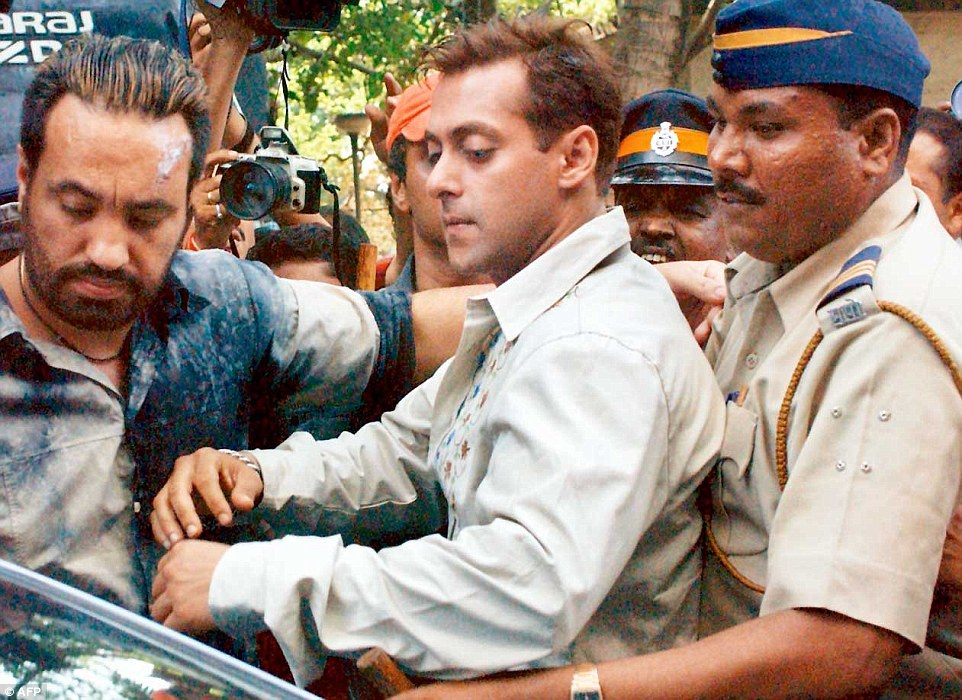 Back at the start: Salman Khan is escorted out of a Mumbai court in October 2003