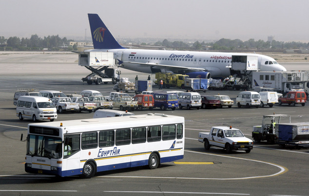 FILE - In this Monday April 21, 2008 file photo, an EgyptAir bus and an EgyptAir plane are seen in Cairo international airport, Egypt. Union officials said W...