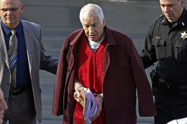 FILE - In this Jan. 10, 2013 file photo, former Penn State University assistant football coach Jerry Sandusky, center, leaves the Centre County Courthouse af...