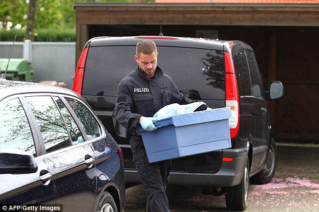 An Investigator loads evidence from the appartment of an allegeded member of a terrorist group