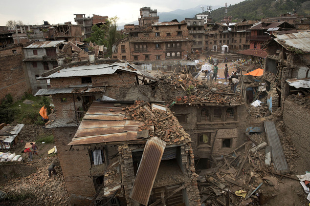 FILE - In this April 29, 2015 file photo, people clear the debris from damage caused by an earthquake in Sakhu, on the outskirts of Kathmandu, Nepal. Sakhu i...