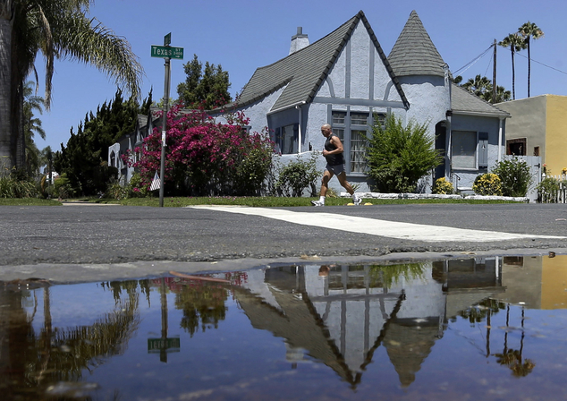 FILE - In this July 9, 2014, file photo, a house is reflected in a puddle of water from an irrigated front yard in San Diego. Californians conserved little w...