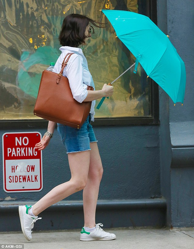 Finishing touches: The 32-year-old actress strode along in white sneakers, concealed her eyes behind aviator shades, and carried a brown tote bag