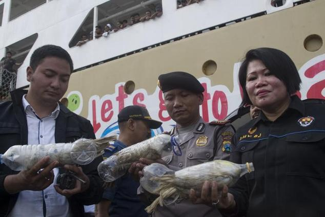 Police and customs officials hold rare Indonesian yellow-crested cockatoos, jammed inside plastic water bottles, confiscated from an alleged wildlife smuggle...
