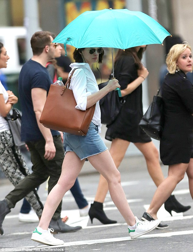 Shade: The brunette beauty unfurled her bright blue umbrella as she crossed the street