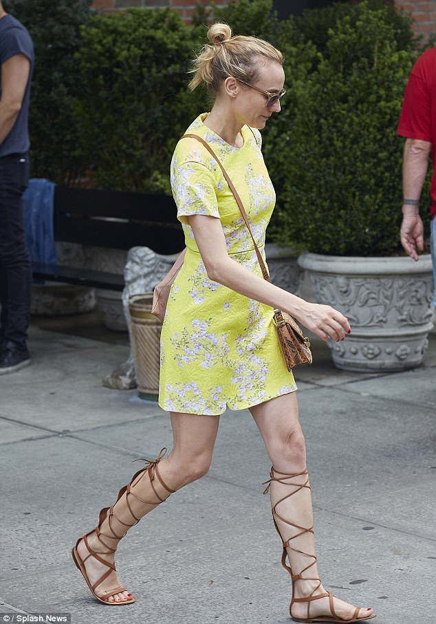 All tied up: Diane Kruger, 38, seen levaing her east Village hotel Tuesday, laced herself up in some gladiator sandals which she paired with a yellow and white floral dess