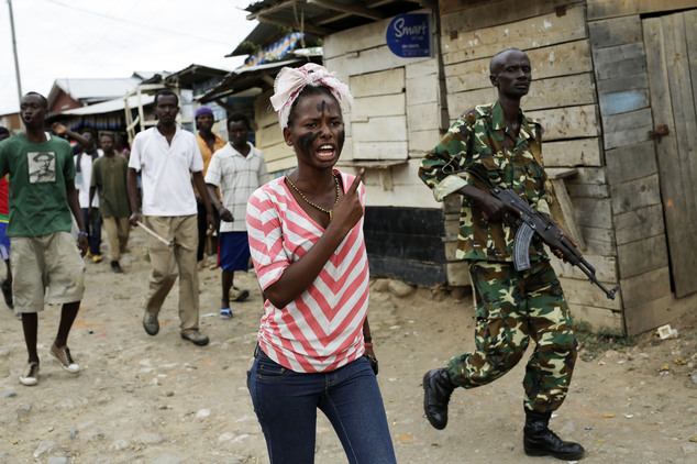 A soldier walks along with demonstrators shouting at police dismantling a barricade in the Kanyosha  district of  Bujumbura, Burundi, Wednesday May 6, 2015. ...