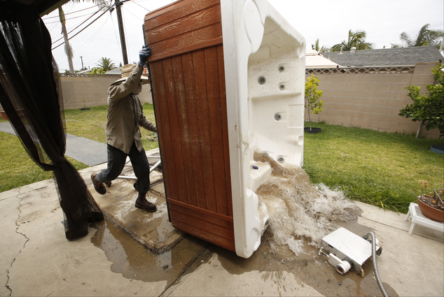 """Professional spa remover Juan Alexander empties a spa for permanent removal at a residence in which the owner considered it """"a waste of water,"""" in  Garden Gr..."""