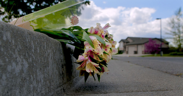 Flowers lie on the 2800 block of West Wilbur Avenue in Coeur d'Alene, Idaho on Tuesday, May 5, 2015, after a police officer was shot  while on duty. Police S...