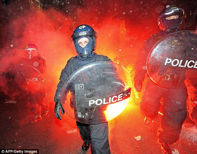 Flashpoint: Police come under attack from flares as they clash with protesters during Thursday's demonstration