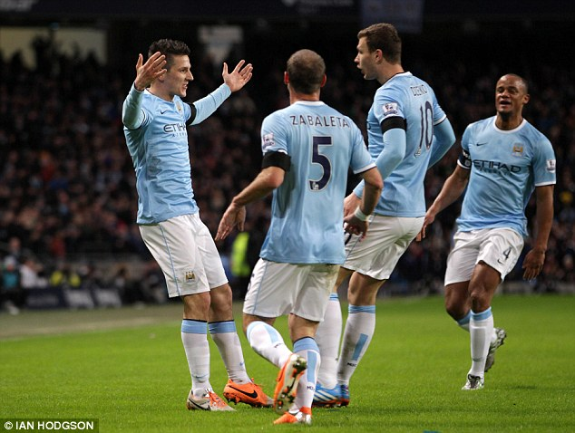 Take that: Jovetic (left) is surrounded by his team-mates after the 16th minute strike