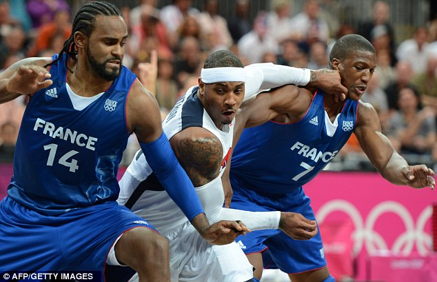 Squeeze: Forward Carmelo Anthony tries to get past two French players