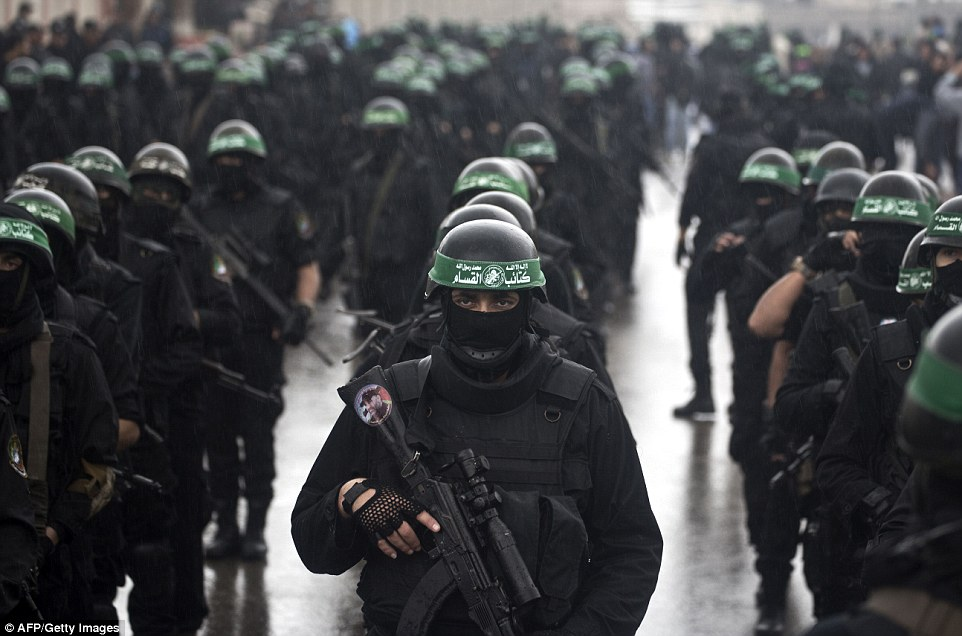 Palestinian militants of the Ezzedine al-Qassam Brigades stand in formation before taking part in the parade through Gaza City today