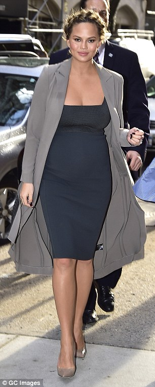 Bumping along nicely! In her first look of the day Chrissy flaunted her growing baby bump as she sported a figure-hugging navy blue pencil skirt dress, along with a flattering grey jacket