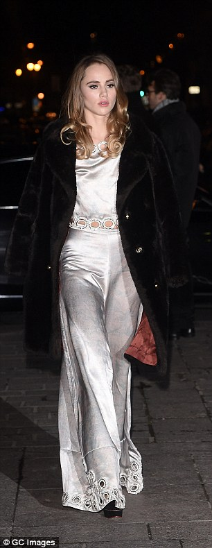 Slinky number: The blonde wore a striking grey silk two-piece, featuring a top with cut out detail at the stomach, showing off her toned abs and a wide pair of matching flares