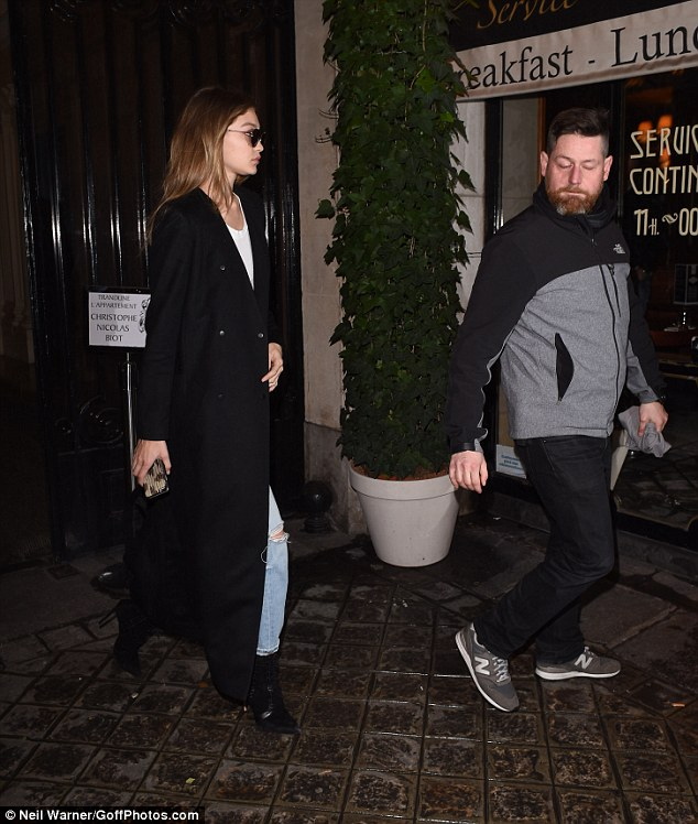 Wrapping up: The style maverick elongated her already lithe legs in a pair of heeled boots, with the lace-up stilettos instilling a touch of glamour into the look, which Gigi finished with a floor-length black duster jacket