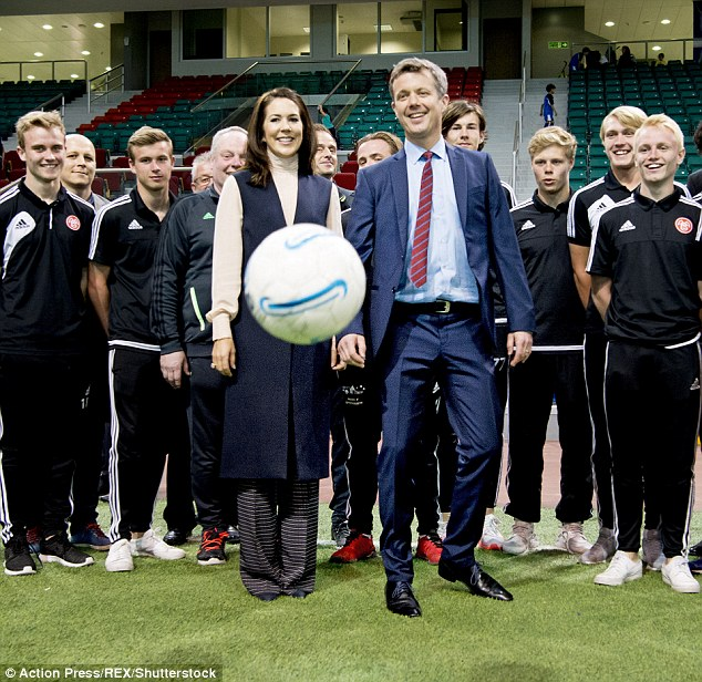 Playful: Despite her conservative get-up, the Princess was all smiles as she posed with staff members and players and playfully kicked the ball around