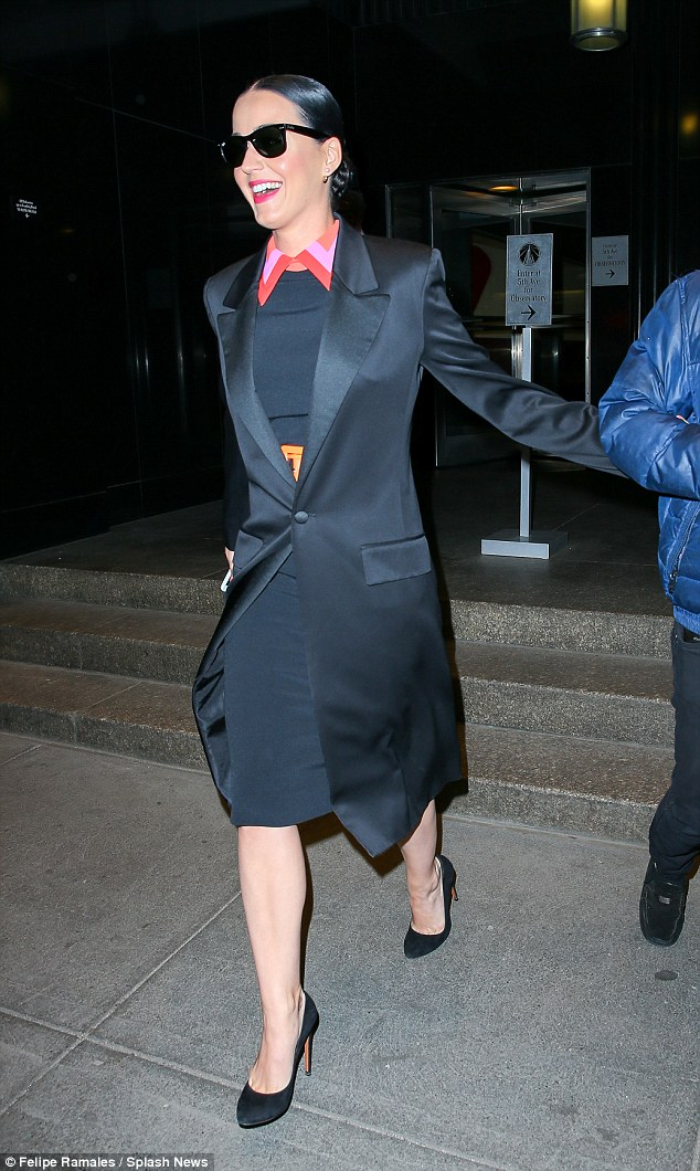 Business chic: Katy sported a fitted black dress with a colourful collar and covered up with a smart coat