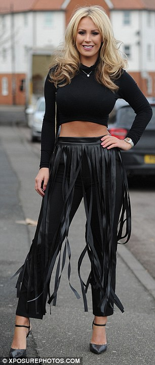 An experimental look: Katie sported a black long-sleeved crop top, a pair of tailored trousers and a slashed leather midi skirt
