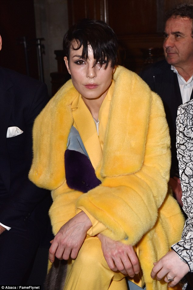 Not-so-mellow yellow: Noomi Rapace once again donned her vibrant canary yellow coat on Thursday morning as she took her place on the front row at the Vionnet Fall/Winter show at Paris Fashion Week