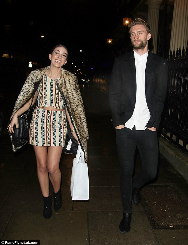 Giddy! The beauty looked in great spirits as she left with her 25-year-old Stevenage defender beau after the bash, goodie bag in hand