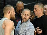 TORRANCE, CA - FEBRUARY 24:  UFC featherweight champion Conor McGregor (L) and lightweight contender Nate Diaz (R) are held apart by Dave Sholler (C), UFC vice president of public relations, after a news conference at UFC Gym February 24, 2016, in Torrance, California.  (Photo by Kevork Djansezian/Getty Images)
