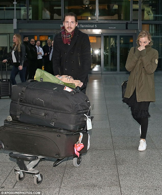 Looking out for his lady! Playing the doting gentleman, Tom wheeled along a trolley of luggage