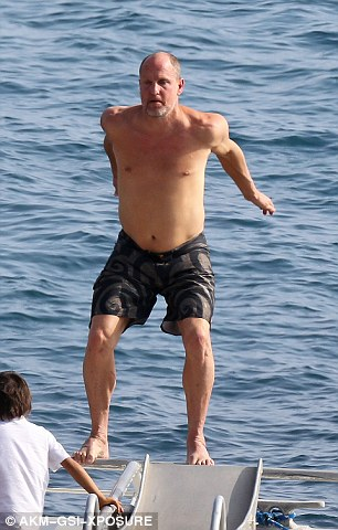 Jump! The Hunger Games actor stripped off his t-shirt to show off his aquatic acrobatic skills, back-flipping into the ocean
