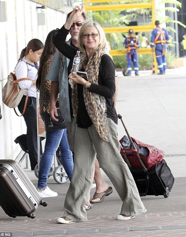 With my baby in Rio:Olivia Newton-John jetted out of Rio de Janeiro, Brazil, to San Paulo withhusband John Easterling on Thursday