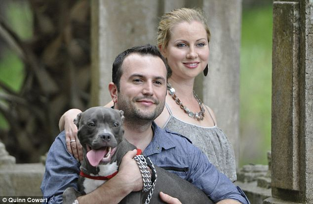 All smiles: Koda is part of the family now, after Eddie Hanna (left) and Melanie Cannon (right) adopted him